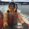 Portrait photo of Hannah Baranes piloting a small boat, smiling and dressed in yellow and orange foul weather gear.
