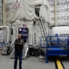 Photograph of Will Daniels standing in larger aircraft hanger with shiny, puffy insulated walls, in front of white, balloon-like space-capsule looking object that will be his home for 45 days.